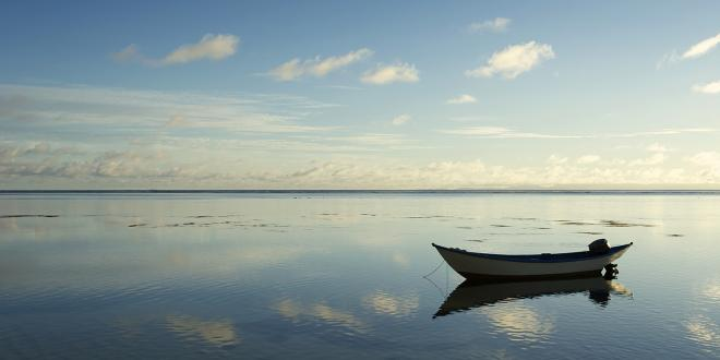 a small boat floating in still and empty waters
